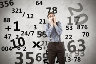 man in front of a screen with numbers