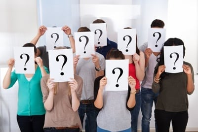 students holding card with question mark