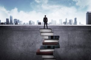 Man on a stack of books to show competency based education