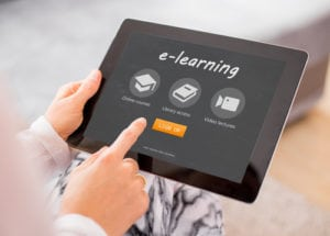Touching a tablet displaying the term eLearning.