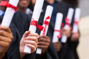 Students with diplomas in hands describing program development.