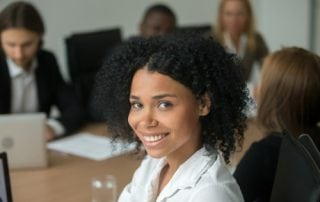 A smiling female instructional designer seated at a table in a workplace.