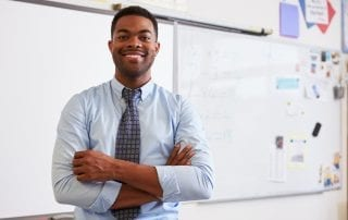 teacher smiling in front of classroom whiteboard